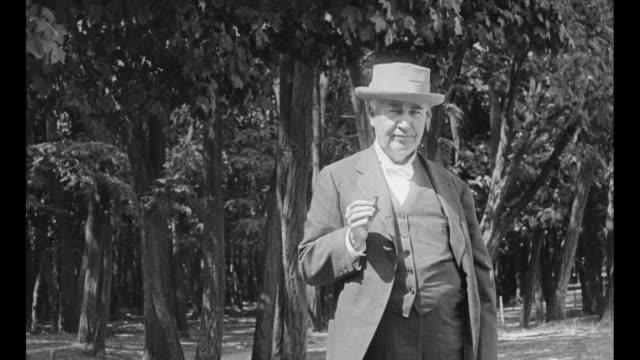 vídeos de stock e filmes b-roll de title card in french / inventor thomas edison standing in front of trees, smoking cigar and posing for photo opportunity / note: exact year not known - 1920
