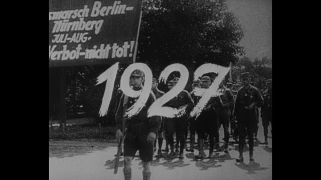 title card in german / brown shirts walk in nuremberg with two bearing sign in german foot march from berlin to nuremberg despite being forbidden not... - braun stock-videos und b-roll-filmmaterial