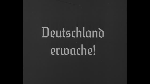 Title card in German Deutschland erwache / Brown Shirts stand with Nazi standard with swastika in metal wreath on finial and NSDAP atop standard...