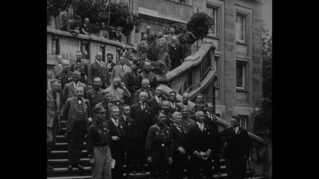 Title card in German loose translation 'other leaders welcome the arrivals' / Adolf Hitler and Nazis some in uniform and some in civilian clothing...