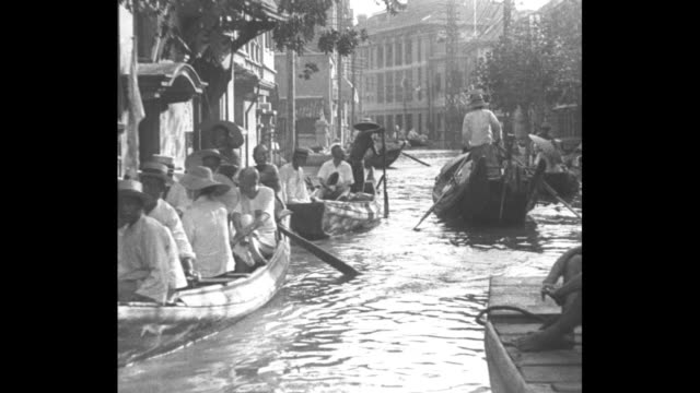 vídeos de stock e filmes b-roll de in hankow industrial metropolis of central china starving refugees crowd flooded streets seeking food / flood victims riding in boats along flooded... - 1931
