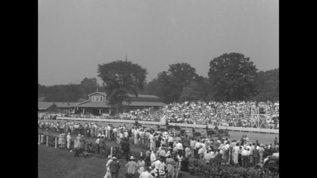 In Harness The Hambletonian Trotting Classic / trotters parade onto track at Good Time Park racecourse / shot of crowd in stands / trotters start...