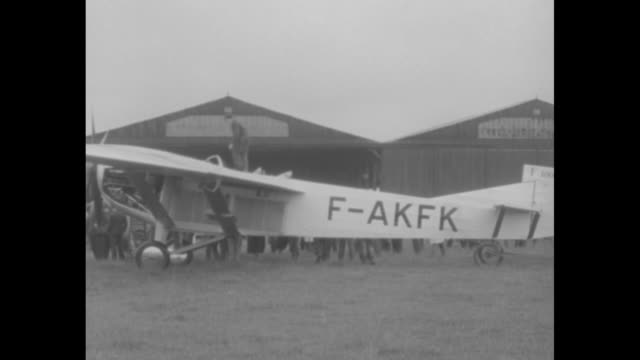 """vidéos et rushes de """"inventor farman tests new stratosphere plane"""" / f 1000 on ground in front of hangars, mechanic on top, can see legs of crowd on other side /... - mécanicien"""