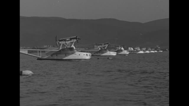 """vídeos de stock, filmes e b-roll de """"italy's sea hawks wing way to rio-orbetello-led by general balbo, 12 seaplanes start goodwill trip of 6417 miles to brazil"""" / seaplanes resting on... - note pad"""