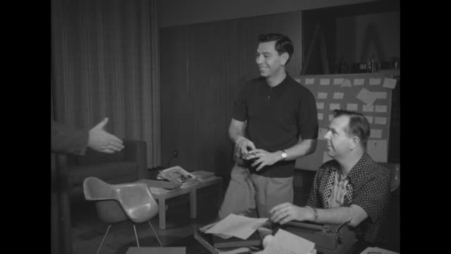 ñjack webb receives his portraitî super imposed over webb and writer / ms actor jack webb smoking a cigarette stands over writer richard breen seated... - open magazine stock videos & royalty-free footage
