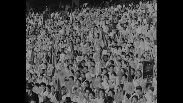vídeos de stock e filmes b-roll de japan hails pact / title tokyojapan superimposed on large stadium rally with japanese german italian rising sun flags flying above / vs views of... - baixar