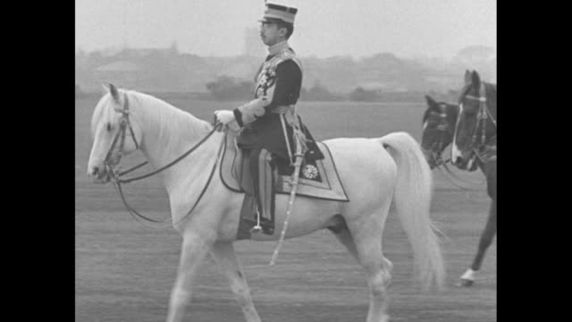 Japan superimposed over slowly swirling smoke / Emperor Hirohito in military uniform rides white horse /soldiers with rifles lie scattered across...