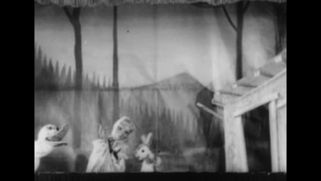 Title card Japan superimposed over theater performance building / title card Spain superimposed over stage with performance of puppet show for...