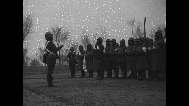 vídeos de stock e filmes b-roll de japanese language title card from nichi nichi international / gv japanese soldiers assemble in countryside field / soldier in winter cap looks... - sampana