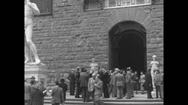 'La Mostra Della Musica' / exterior of Galleria dell'Accademia with Michelangelo's David / people talking outside bronze doors of Florence Baptistery