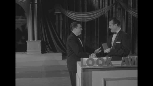 look awards salute top 1954 stars superimposed over ms award presenter red skelton as he smiles and kisses an award plaque / ws skelton hands film... - plakette stock-videos und b-roll-filmmaterial
