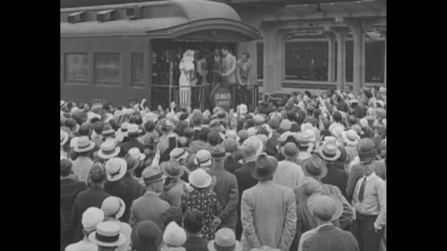 """""""los angeles greets aimee mcpherson"""" / evangelist amy semple mcpherson with grandchild and bouquet in arms stands with others on rear platform of... - preacher stock videos & royalty-free footage"""