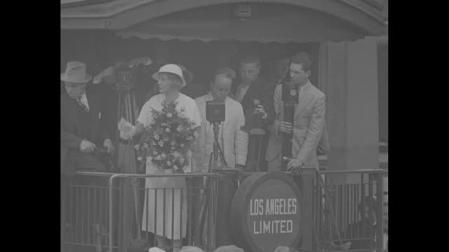 """""""los angeles greets aimee mcpherson"""" / mcpherson holding grandchild and bouquet stands with others on rear platform of railcar, greeting crowd all... - preacher stock videos & royalty-free footage"""
