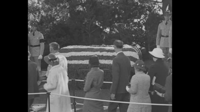 vídeos de stock, filmes e b-roll de los angeles superimposed over an aerial view of forest lawn cemetery with long lines of people / people walk through an iron gate / casket with honor... - charlie chaplin