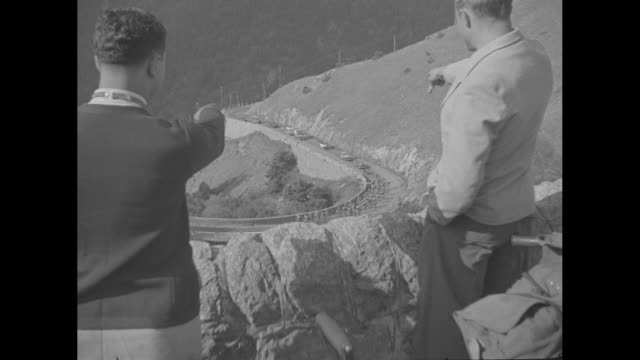 maes victor in 3000mile bicycle race / rear shot two men in foreground watch race from hillside point as participants in the tour de france race... - torre dell'orologio torre video stock e b–roll