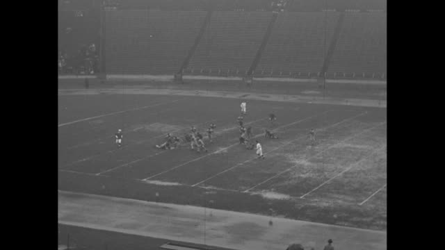 "vidéos et rushes de ""maryland defeats hopkins"" / maryland terrapins team starts football game in the rain on muddy field at municipal stadium with kickoff to johns... - maryland état"