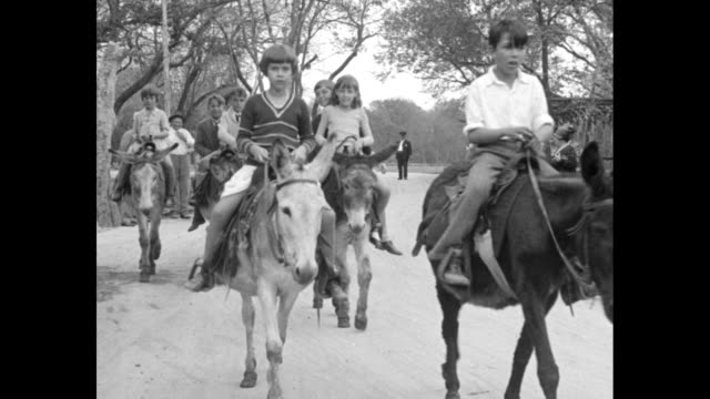 'Match pet burros in unique contest San Antonio Texas Youngsters of Southwest ride prize donkeys in championship contest' / children on burros riding...