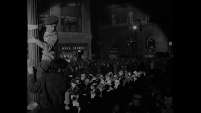 mayorelect la guardia thanks you/ crowd gathered at night in times square / crowd cheering waving / two spotlights shining on crowd / boy on pole... - fiorello la guardia stock videos & royalty-free footage