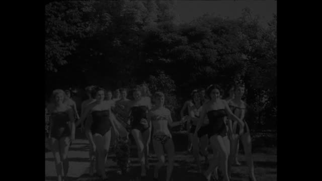 vídeos de stock, filmes e b-roll de meet miss france superimposed over cu of claude godard miss france / mws contestants in bikinis run out from behind trees and bushes / mspan... - rainha de beleza