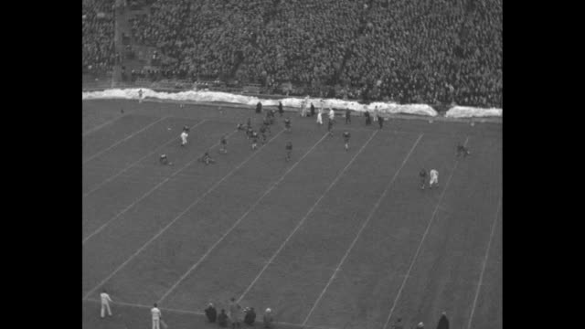 'Michigan Tied By Minnesota' / WS filled stadium and football game on snow lined field crowd cheers plays include interceptions and field goal