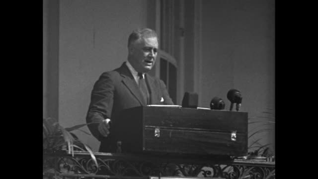 vídeos de stock e filmes b-roll de superimposed over fade in to pres. franklin roosevelt at podium / roosevelt speaks from podium from white house portico, rear view of audience in... - fade in