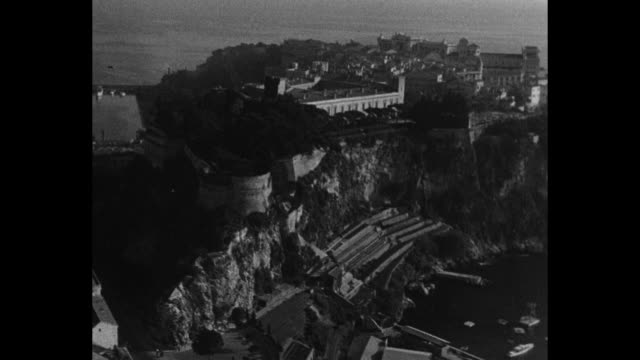 'Monaco Jour de fete a MonteCarlo' / Pan cross view of Monte Carlo and Mediterranean Sea beyond / people walking up outdoor stairway up to archway of...