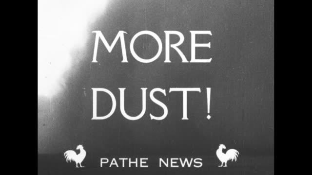 vidéos et rushes de more dust superimposed over thick midwest dust storm / women in office filing / cu man / starving cattle / cu cow nibbling on dry dirt / farm... - tempête de poussière