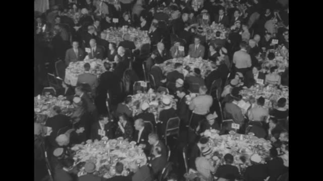 """""""movie industry communion breakfast"""" / tilt-down grand ballroom of waldorf astoria hotel, with representatives of the film industry seated at round... - hotel waldorf astoria stock-videos und b-roll-filmmaterial"""