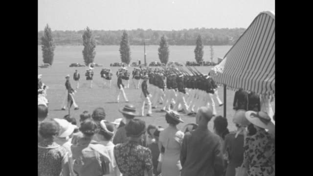 """""""navy leads graduation parade,"""" then superimposed over cadets in dress uniforms on field lifting hats / cadets at attention on field, rear admiral... - 士官候補生点の映像素材/bロール"""
