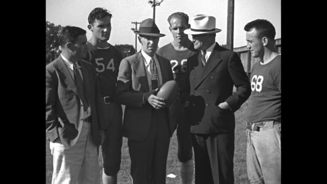 """vidéos et rushes de """"new stars for boston redskins"""" / boston redskins coach eddie casey kneeling beside three new players and sot giving them instructions as they run... - nfc"""