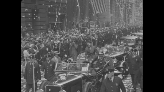 'New York Acclaims Wiley Post' / New York City ticker tape parade / aerials of flags over confetticovered streets / police escort motorcade / Wiley...