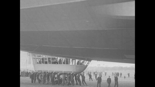 """new zep crosses ocean"" / the tail portion of the towering airship with a swastika on its fin leaves its hangar / vs with people holding onto its... - newsreel stock videos & royalty-free footage"