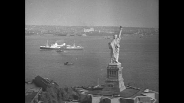 vidéos et rushes de 'news flashes' /aerial pov of the s s pilsudski steaming into new york harbor beyond the statue of liberty / view of ship accompanied by tug boats /... - statue de la liberté