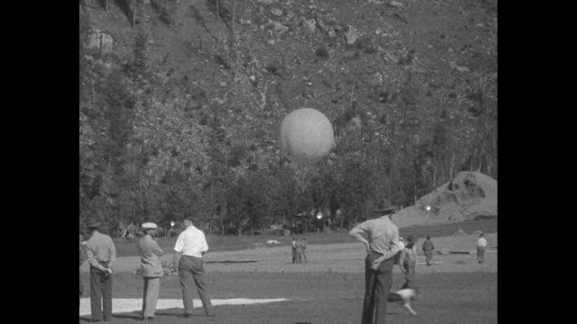 vídeos de stock e filmes b-roll de news flashes / aerial view of moonlight valley bowl where preparations for launch are being made / two shots of men preparing to launch small balloon... - rapid city