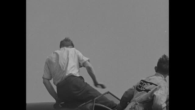 """–news flashes"""" / charles lindbergh climbs atop plane steps down with wife anne / with foot on running board lindbergh writes as anne looks on / the... - charles lindbergh stock videos & royalty-free footage"""