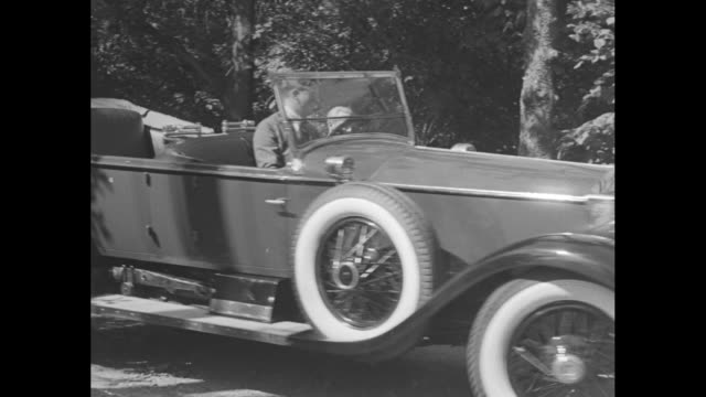 """news flashes!"" / close shot of john jacob astor vi pulling away in his rolls royce / astor pulling away / shot of exterior of astor's ornate house... - rolls royce stock videos & royalty-free footage"