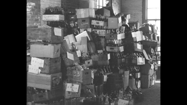 news flashes dry agents smash holiday cheer valued at $250000 in new york / men move pallets with crates of alcohol / stacked crates of alcohol /... - 1930~1939年点の映像素材/bロール