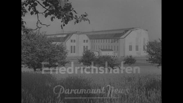 news flashes from abroad / friedrichshafen superimposed on zeppelin hangars / dr hugo eckener with others at conference table / engineers draft... - germany stock videos & royalty-free footage