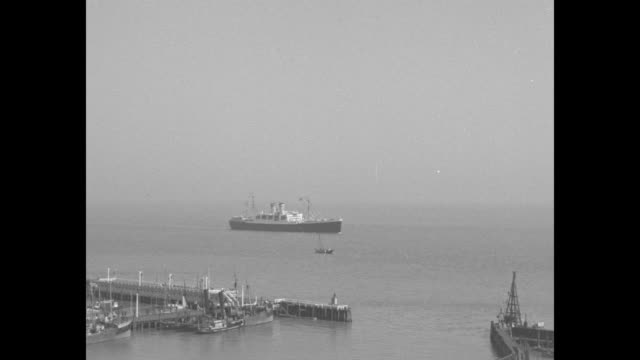 """""""news flashes from abroad"""" / title: """"cuxhaven, germany"""" superimposed over ship in harbor / soldiers stand at attention as ship arrives; crowd watches... - passagierschiff stock-videos und b-roll-filmmaterial"""