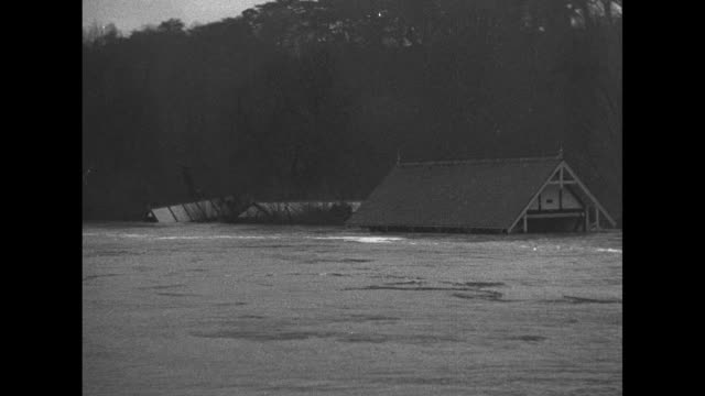 'News Flashes from Abroad' / Title 'Thames Valley England' superimposed over flooded river flowing past house / CU water in river churning / house is...