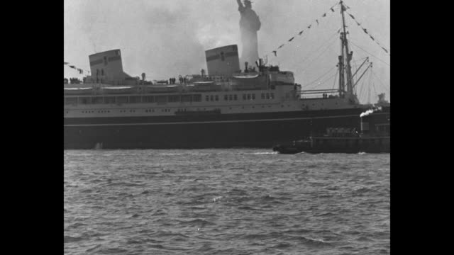 News Flashes from Everywhere / New York City superimposed on ship passing Statue of Liberty / VS ship MS Pilsudski passes statue aerial view ground...
