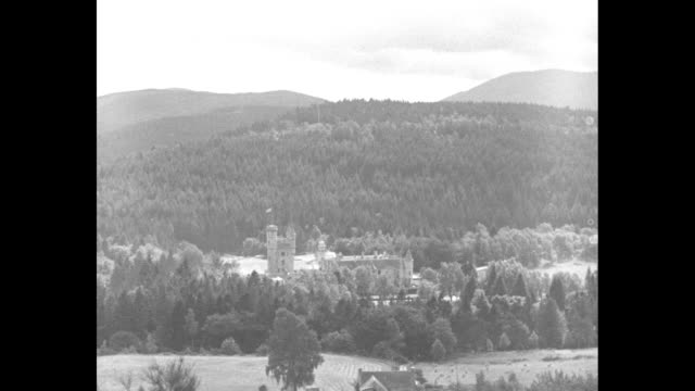 News Flashes From Everywhere / title Ballater Scotland superimposed over MS EXT Balmoral Castle with Royal Standard flying atop / montage King George...