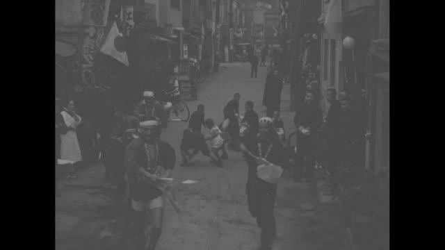 news flashes from everywhere / title tokyo japan superimposed men throwing papers in street followed by children picking up papers / cu papers in... - 1930~1939年点の映像素材/bロール