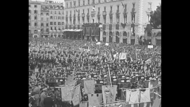 vídeos de stock, filmes e b-roll de news flashes italian fascists march with banners and flags at mussolini rally in piazza / huge crowd running in piazza / stage with benito mussolini... - benito mussolini