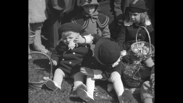"""""""news flashes!"""" / large crowd of egg-rolling children on lawn in front of the white house/ two kids sitting on lawn with their easter baskets /... - påsk bildbanksvideor och videomaterial från bakom kulisserna"""