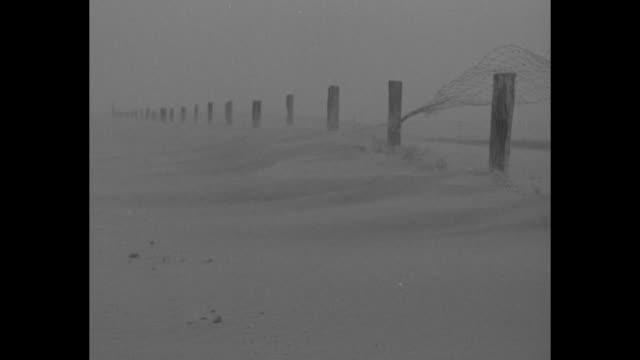 news flashes / ms man walks across farm area as dust storm blows dust partially submerged building stands in background near windmill / wind blows... - den stora depressionen nyhetshändelse bildbanksvideor och videomaterial från bakom kulisserna