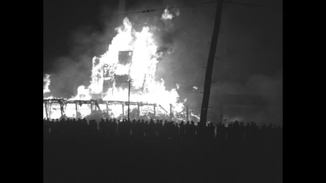 News Flashes / night VS Chesapeake and Ohio Railway grain elevator burns in Virginia with flames burning brightly against night sky / firefighters...