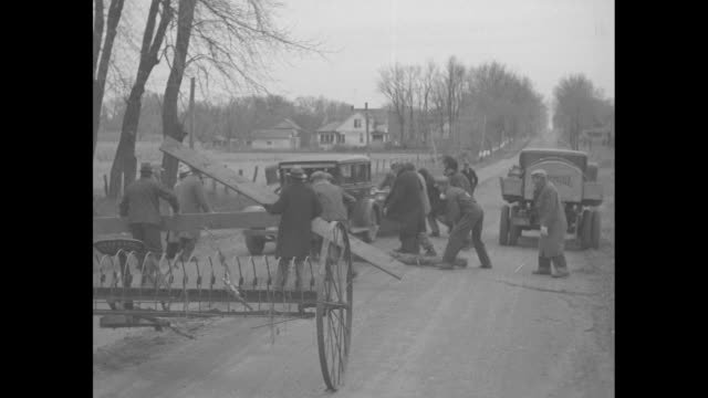 """""""news flashes!"""" / supporting idea of farmers' holiday, farmers blockade road and force approaching car pulling trailer to pull off road / two shots... - great depression stock videos & royalty-free footage"""