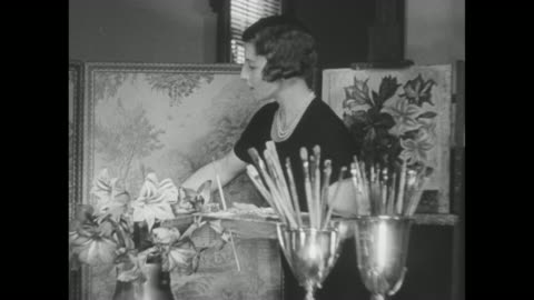 """""""news flashes!"""" / tennis player helen wills moody, wearing a black dress and pearls, takes her place at an unfinished painting, she arranges flowers... - schwarzweiß bild stock-videos und b-roll-filmmaterial"""