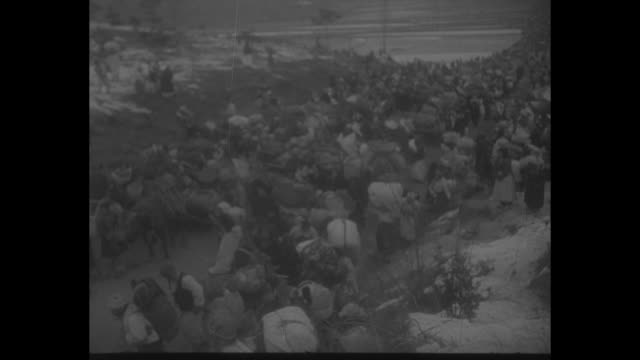 stockvideo's en b-roll-footage met news roundup / title the war in korea superimposed over crowd of refugees carrying their belongings and hauling them in wagons moving down road /... - koreaanse oorlog